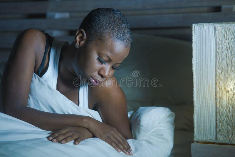 Livsstilnattstående av den unga ledsna och stressade svarta afrikansk amerikankvinnan som ligger på sängrubbningen som försöker a arkivfoto