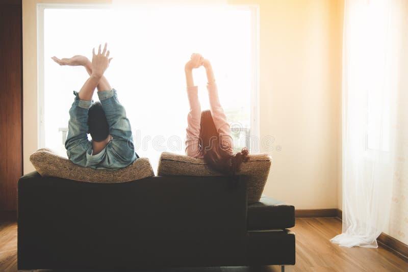 Livsstilpar som är förälskade och kopplar av på en hemmastadd soffa och utanför ser till och med fönstret av vardagsrummet royaltyfria foton