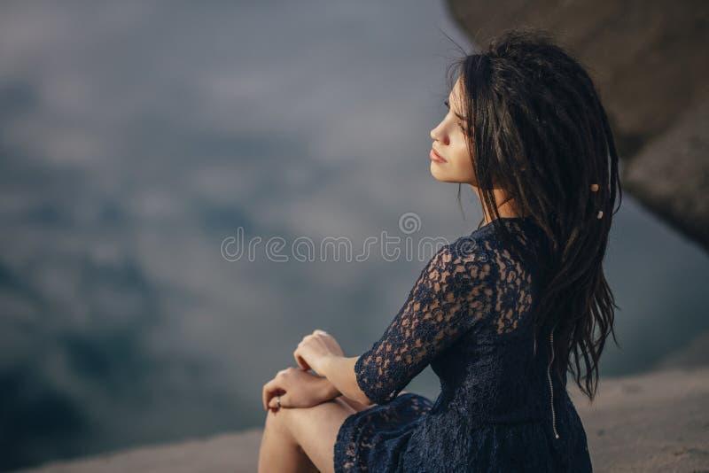 Livsstilstående av brunetter för en kvinna i bakgrund av sjösammanträde i sand på en molnig dag Romantiker försiktigt som är myst royaltyfria bilder
