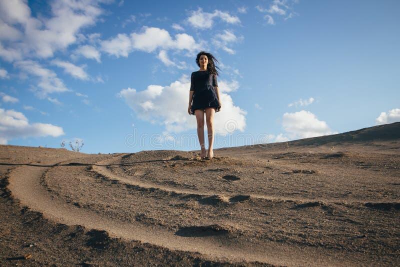 Livsstilstående av brunetter för en kvinna som studsar i sanden om den klara dagen Romantiker försiktig, mystisk eftertänksam bil arkivbild
