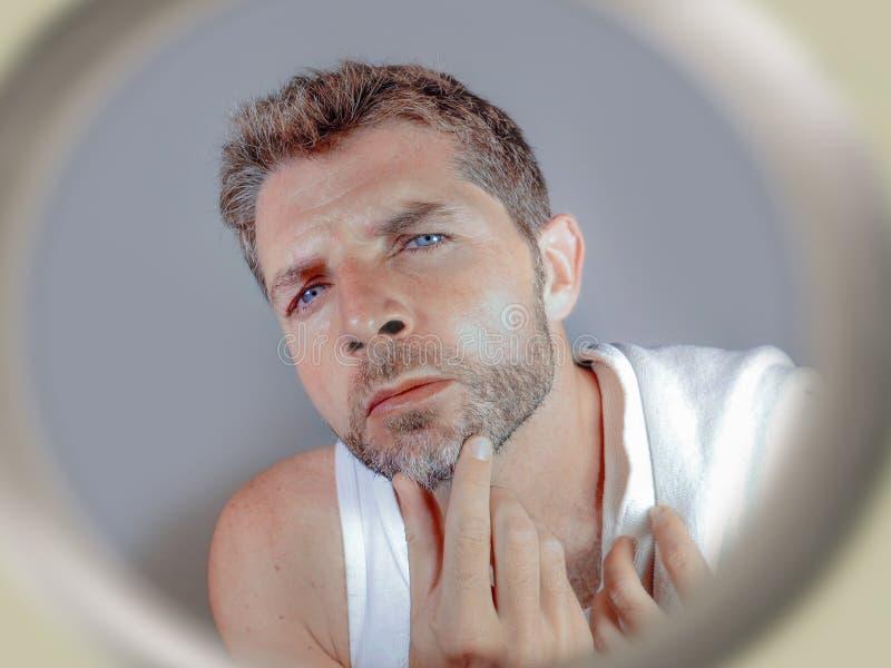 Livsstilstående av den attraktiva bekymrade och bekymrade Caucasian mannen som ser badrumspegeln som finner mer grått hår i skägg royaltyfria foton