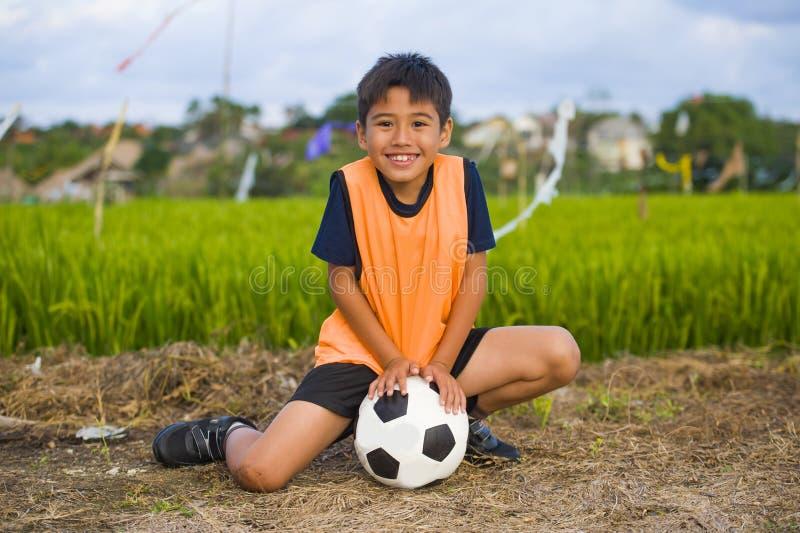 Livsstilstående av den hållande fotbollbollen för stilig och lycklig ung pojke som utomhus spelar fotboll på fältet för grönt grä royaltyfria foton
