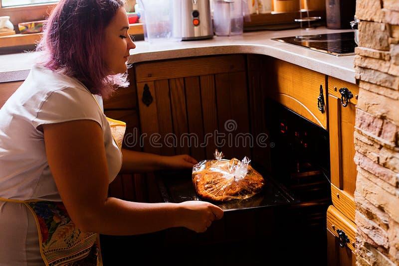 Livsstilstående av den lyckliga matlagningkalkon och grönsaker för ung kvinna för tacksägelsematställe fotografering för bildbyråer