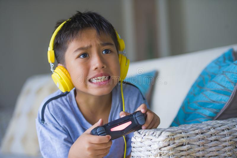Livsstilstående av den unga latinska liten upphetsade och lyckliga spela videospelet för unge direktanslutet med hörlurar som rym arkivfoto