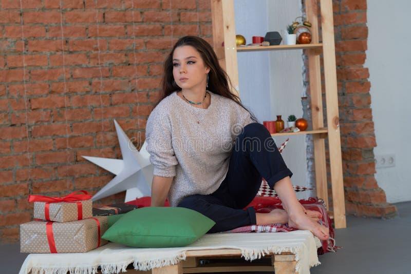 Livsstilstående av den unga lyckliga kvinnan som poserar l hemmastatt sitta för sovrum som är styggt på säng, i att se för pyjama royaltyfria foton