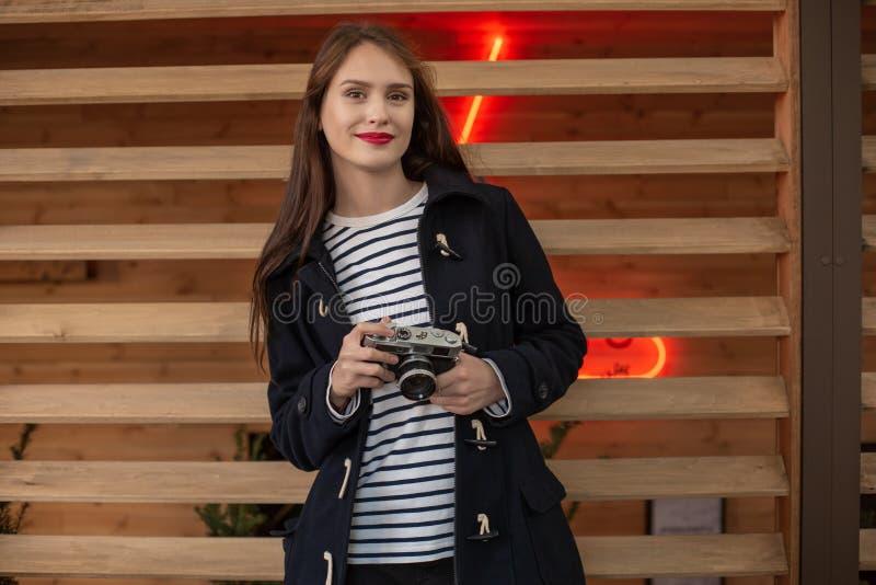 Livsstilstående av den unga stilfulla kvinnan som går på gatan, med kameran som ler för att tycka om helger royaltyfria bilder