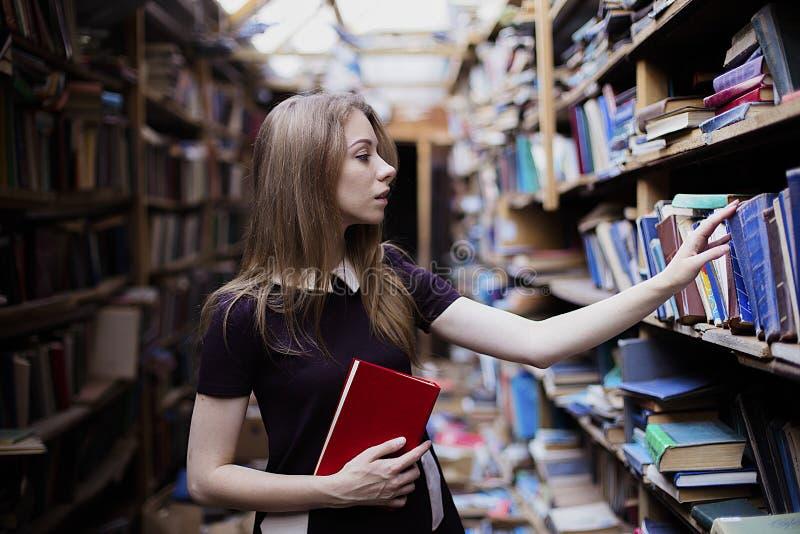 Livsstilstående av en älskvärd studentflicka i tappningarkiv eller bokhandel royaltyfri fotografi