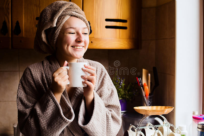Livsstilstående av en härlig ung flicka som dricker morgonkaffe i hennes kök arkivfoto