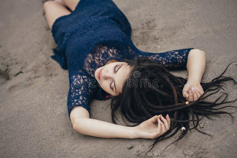 Livsstilstående av en kvinnabrunett på bakgrund av sjön som ligger i sand på en molnig dag Romantiker försiktigt som är mystisk royaltyfri fotografi