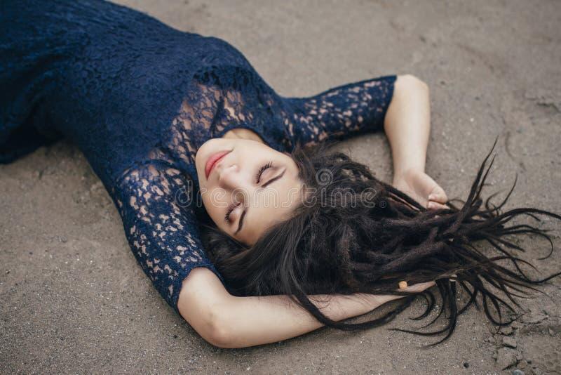 Livsstilstående av en kvinnabrunett på bakgrund av sjön som ligger i sand på en molnig dag Romantiker försiktigt som är mystisk arkivfoto