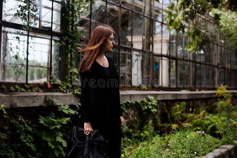 Livsstilstående av t-skjortan, jeans och laget för mellanrum för flicka som den bärande svarta poserar mot byggnad som täckas med arkivbild