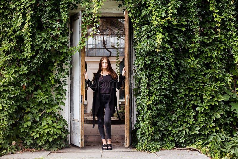 Livsstilstående av t-skjortan, jeans och laget för mellanrum för flicka som den bärande svarta poserar mot byggnad som täckas med arkivbilder