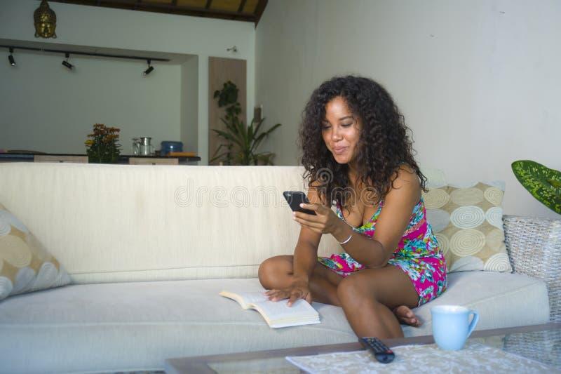 Livsstilstående av ungt nätverkande och att smsa för mobiltelefon för lycklig och härlig latinsk kvinna som hemmastadd användande royaltyfria foton