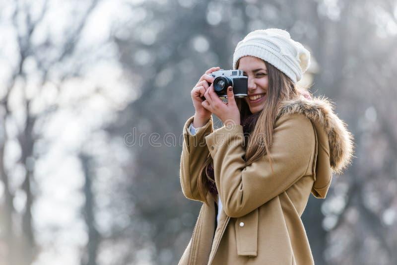 Livsstilstående av vinterflickan med tappningkameran royaltyfri foto