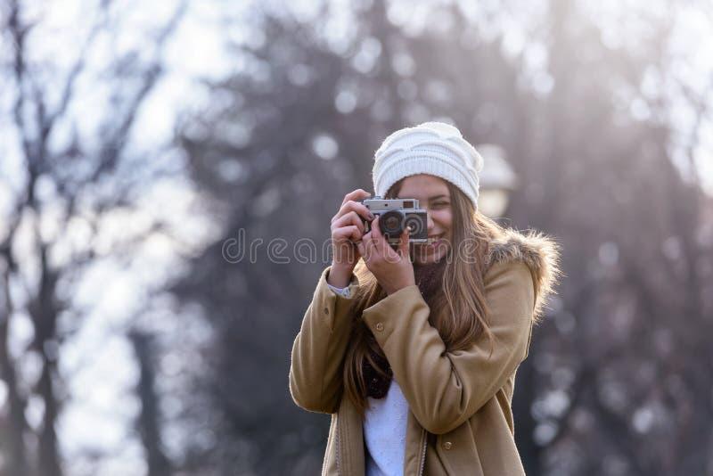 Livsstilstående av vinterflickan med tappningkameran royaltyfri fotografi