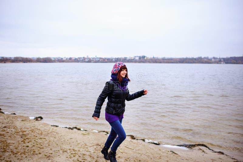 Livsstilståenden av den slanka kvinnan för den unga caucasianen kör längs strandhöst arkivbilder