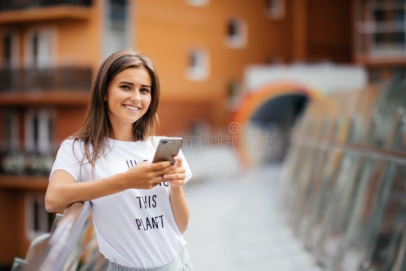 Livsstilståenden av en kvinna klädde tillfälligt att stå med telefonen på den moderna bron arkivbild