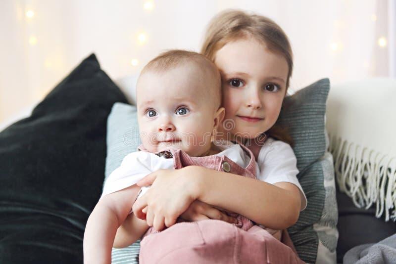 Livsstilståenden av gulliga Caucasian små flickasystrar som rymmer, behandla som ett barn på säng royaltyfri bild
