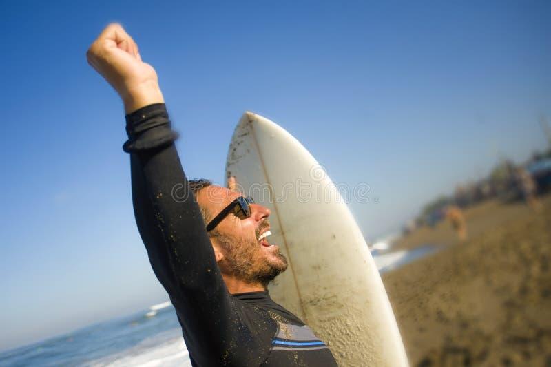 Livsstilst?ende av den attraktiva och lyckliga surfaremannen 3os till 40-tal i neoprene som surfar baddr?kten som poserar med br? arkivfoto