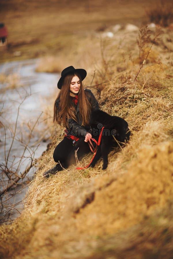 Livsstilst?ende av den unga kvinnan i svart hatt med hennes hund som vilar vid sj?n p? en trevlig och varm h?stdag arkivfoton