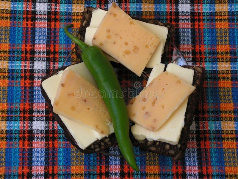 1 livstid fortfarande sm?rg?sar R?gbr?d med sm?r, ost och chilipeppar arkivfoton
