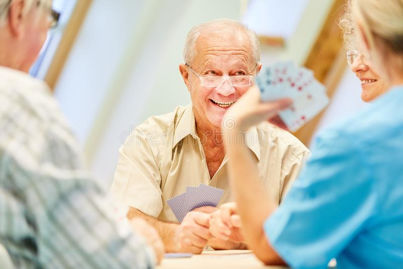 Livsviktiga pensionärer tycker om spela kort arkivfoton