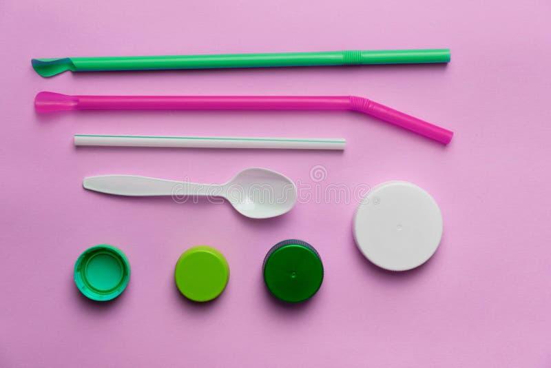 Lixo da colher da palha do tampão da tampa ou questão meio-ambiental azul verde plástica colorida do lixo no fundo cor-de-rosa fotos de stock royalty free