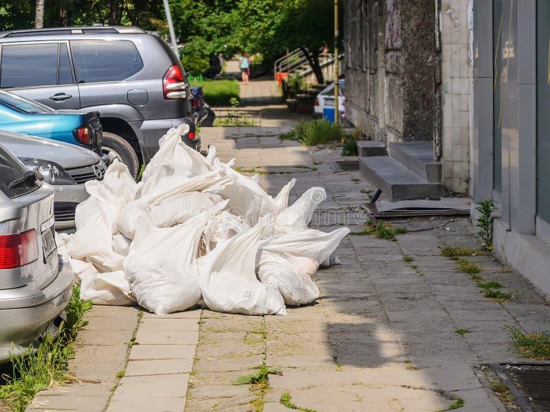 Lixo da constru??o ap?s o reparo do apartamento Pilha do desperdício da construção nos sacos brancos perto de uma construção resi imagens de stock royalty free