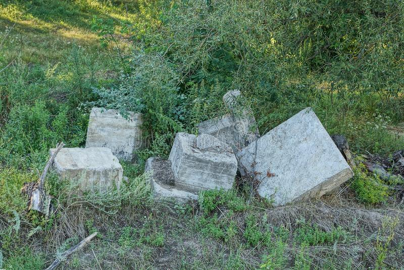 Lixo das partes cinzentas de blocos de cimento na grama verde fotografia de stock