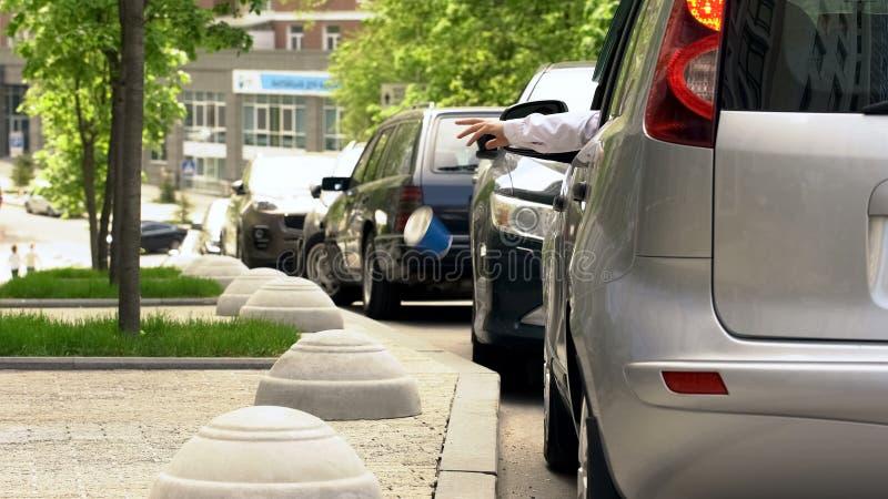 Lixo de jogo do motorista fora da janela de carro, contaminação na cidade, passeios sujos imagens de stock royalty free