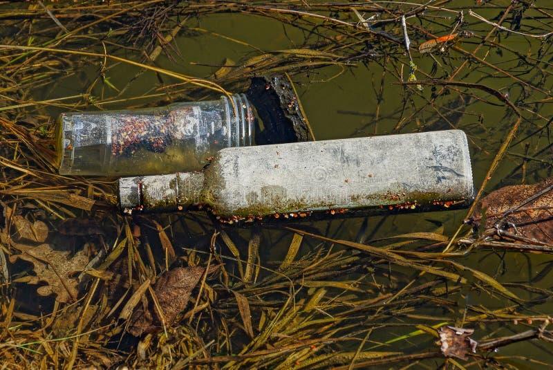 Lixo de uma garrafa de vidro cinzenta e de uns vidros plásticos na água do lago imagens de stock royalty free