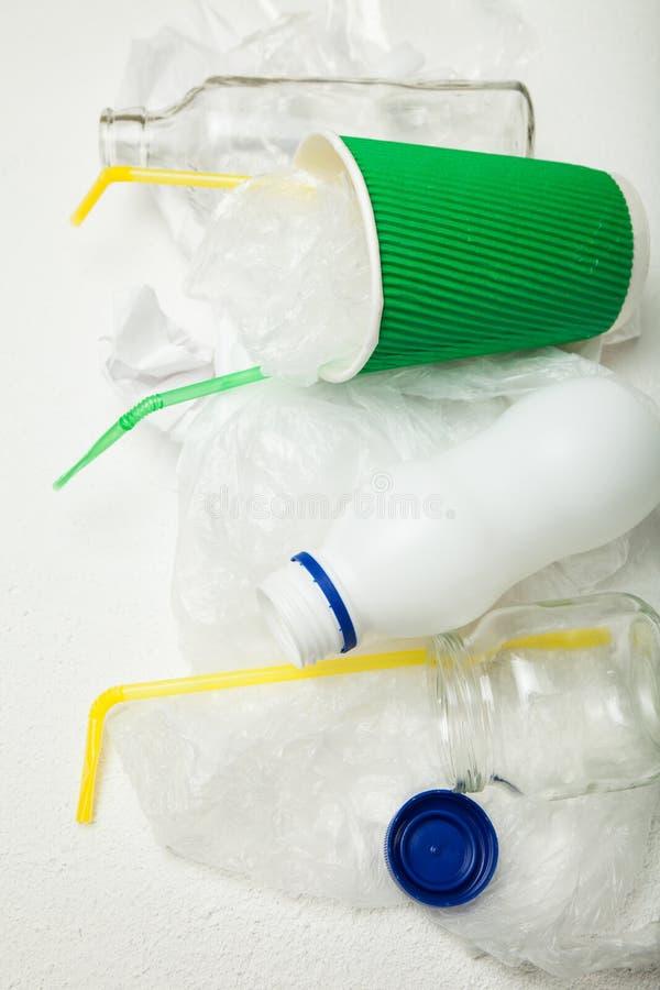 Lixo derramado: garrafas do empacotamento de alimento, de um copo de papel e dos tubos plásticos recycling fotografia de stock royalty free