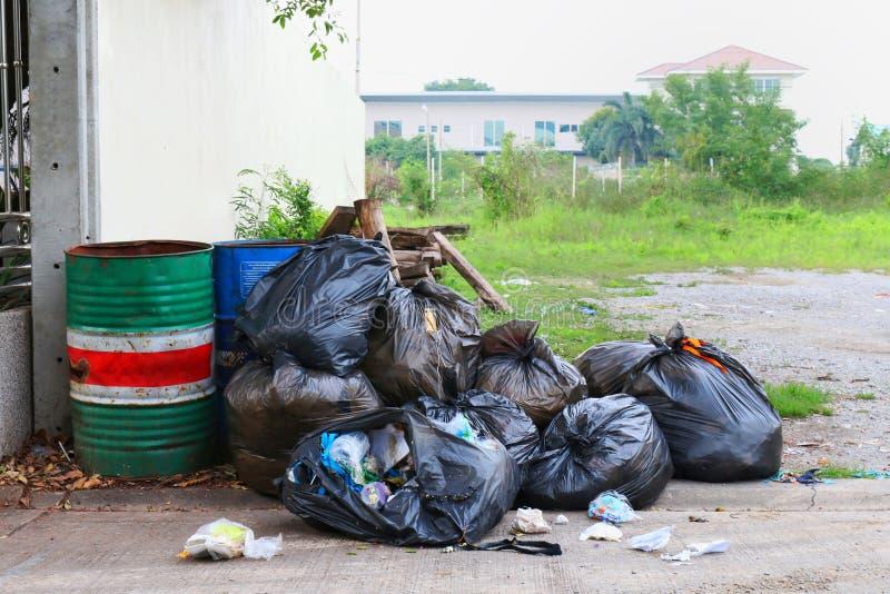 Lixo do escaninho da poluição, lixo do preto do saco do escaninho ao lado do escritório domiciliário da cerca na rua, 3R imagem de stock