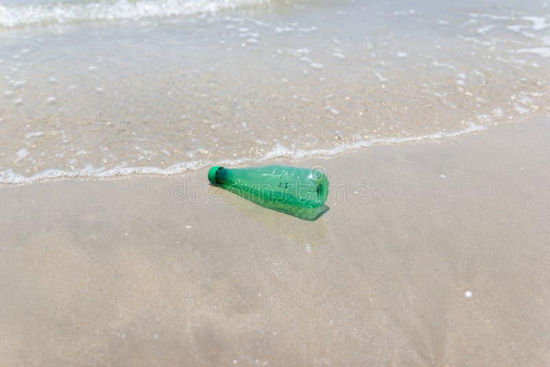Lixo e desperdício plástico do garrafa e o sujo em uma praia foto de stock