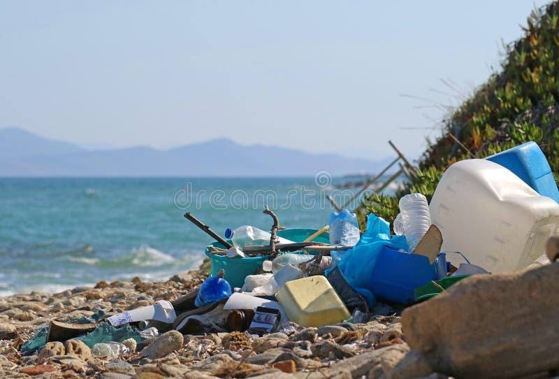 Lixo e desperdícios plásticos na praia com o mar e uma ilha no fundo imagem de stock