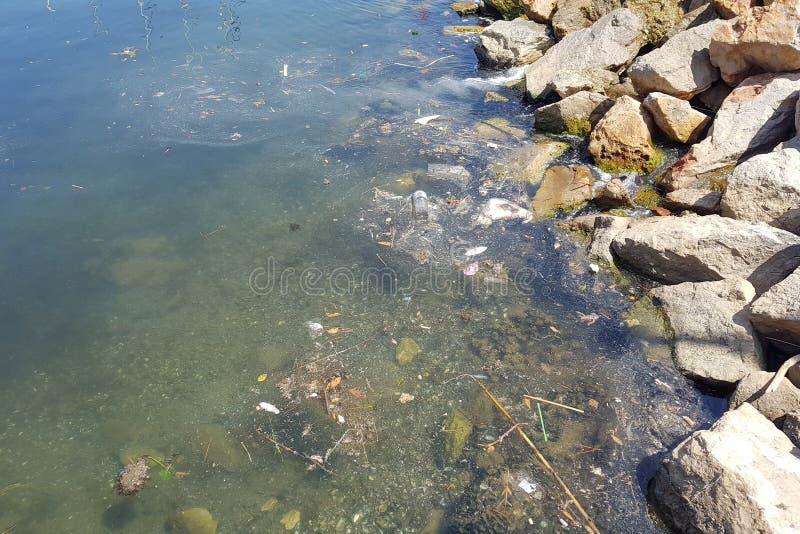 Lixo e saco de plástico na água do mar litoral imagem de stock