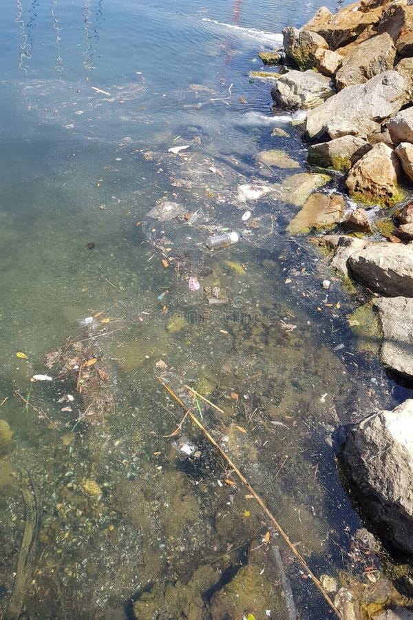 Lixo e saco de plástico na água do mar litoral fotografia de stock