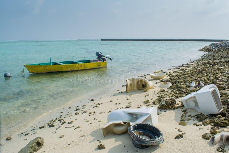 Lixo e toaletes quebrados na praia tropical imagens de stock