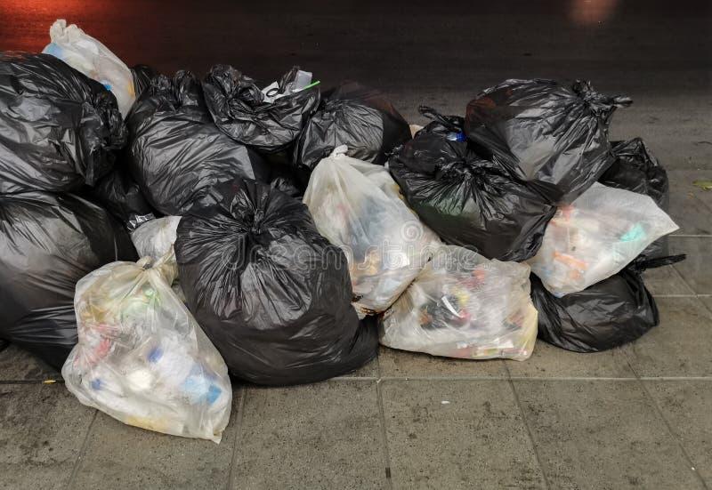 Lixo - o montão de lixo no saco preto e branco é unido sobre o passeio, borda da estrada na cidade, espera para o lixo fotografia de stock