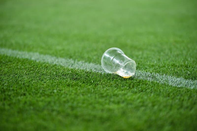 Lixo plástico no relvado em um campo de futebol foto de stock royalty free