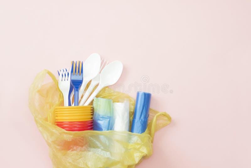 Lixo pl?stico Uma foto de cima dos utensílios de mesa, das colheres, das forquilhas, dos copos e dos sacos descartáveis plásticos foto de stock