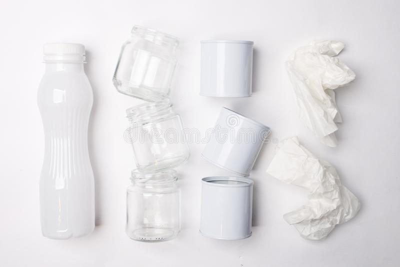 Lixo reciclável que consiste no vidro, no plástico, no metal e no papel no fundo branco Conceito branco da textura fotografia de stock royalty free