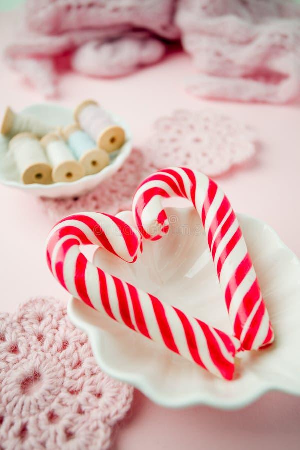 Lizaków cukierki jak serce na różowym pastelowym rocznika tle Pojęcie słodcy romantyczni sensy zdjęcia stock