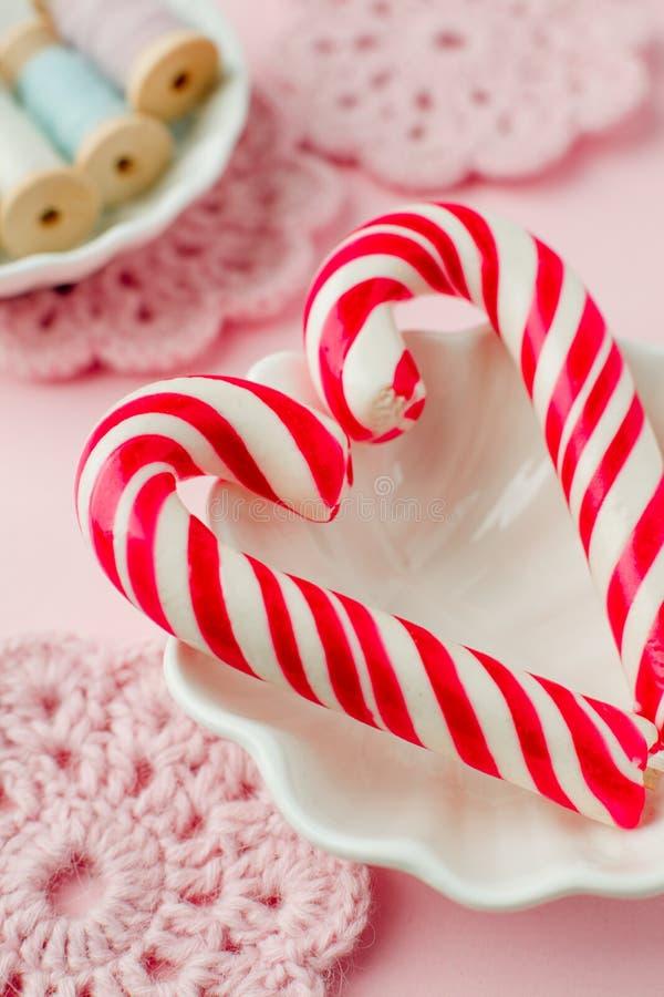 Lizaków cukierki jak serce na różowym pastelowym rocznika tle Pojęcie słodcy romantyczni sensy obraz royalty free