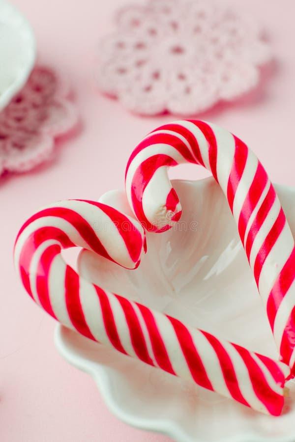 Lizaków cukierki jak serce na różowym pastelowym rocznika tle Pojęcie słodcy romantyczni sensy obraz stock