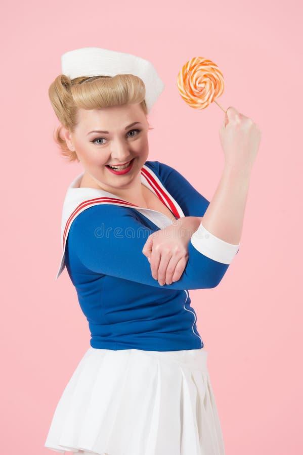 Lizak może robić najlepszy pojęciu Pomarańczowy duży lizak w ręce atrakcyjna blondynki kobieta z kędziorami i żeglarz mundurujemy zdjęcia stock
