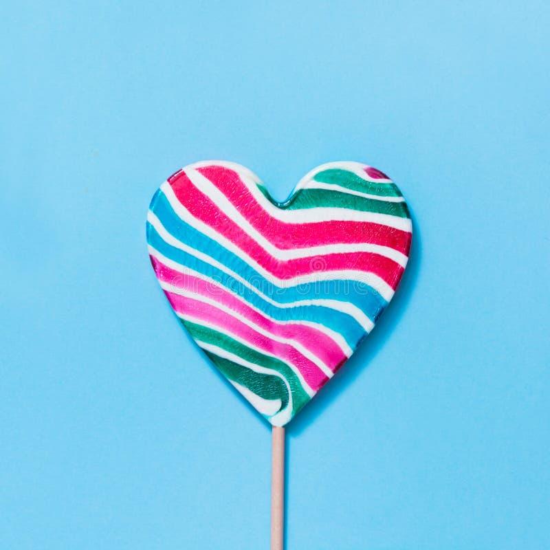 Lizak tęczy kolorowy stripy cukierek jako serce na błękicie Śmieszny pojęcie Odgórny widok Kwadratowy wizerunek obraz royalty free