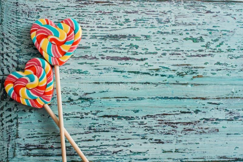 Lizak tęczy kolorowy stripy cukierek jako serce na błękitnym tle Śmieszny pojęcie obrazy royalty free