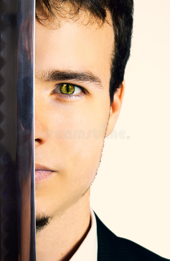 Lizard man. Half face of a suited lizard eyed man, holding a katana sword stock image