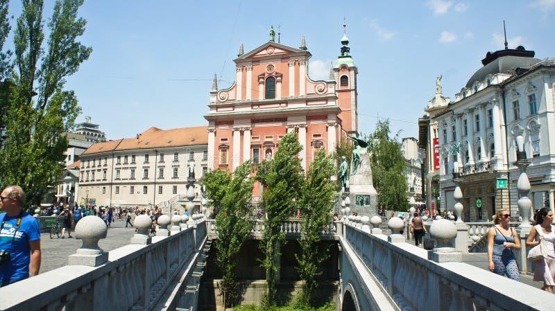 Ljubljana, Eslovenia - 07/19/2015 - puentes triples del puente 3 a través de Ljubljanica e iglesia franciscana en el centro de ci fotografía de archivo libre de regalías